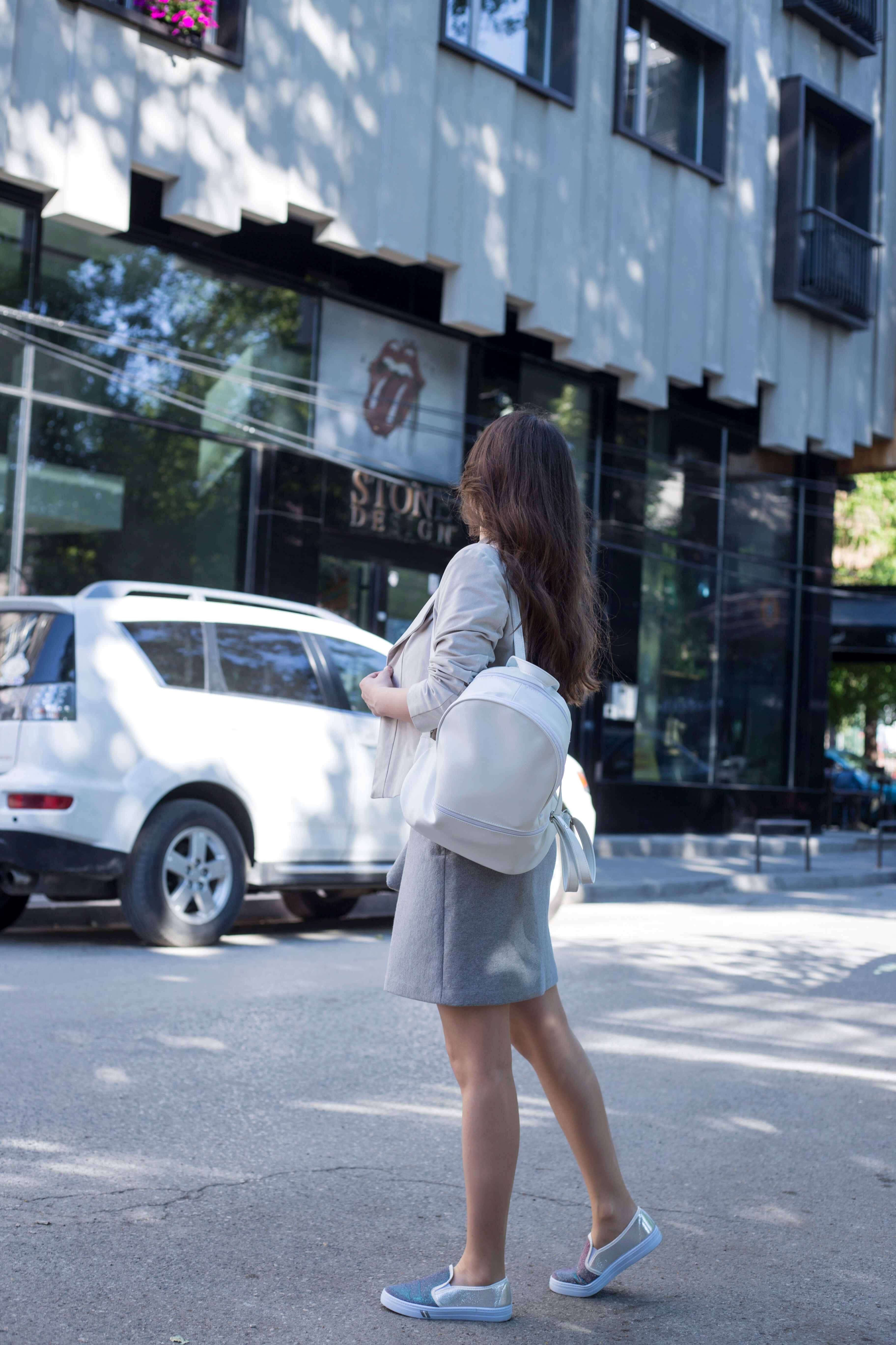 Wearing a white backpack, gray skirt, and color-shifting slip ons on www.dilekaspires.com